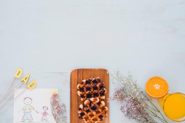 Waffles y jugo cerca de flores y dibujo