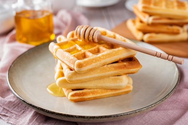Waffles con miel sobre un fondo claro