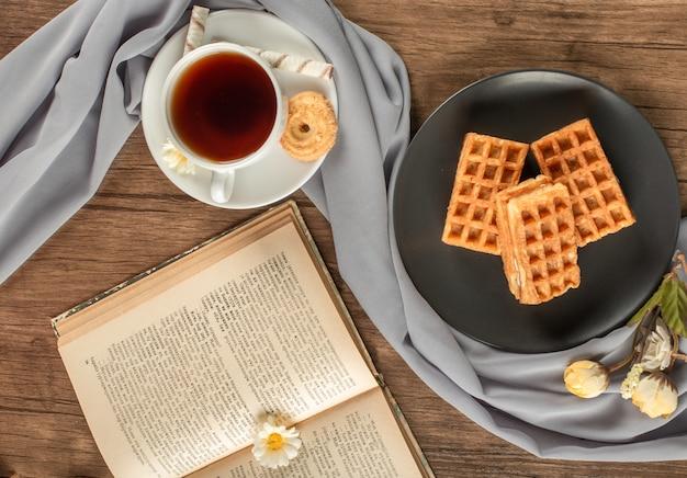 Waffles en un plato negro, una taza de té y un libro. vista superior