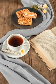 Waffles en un plato negro, una taza de té y un libro.