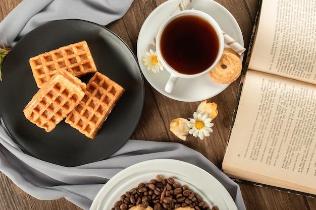 Waffles en un plato negro y una taza de té. vista superior