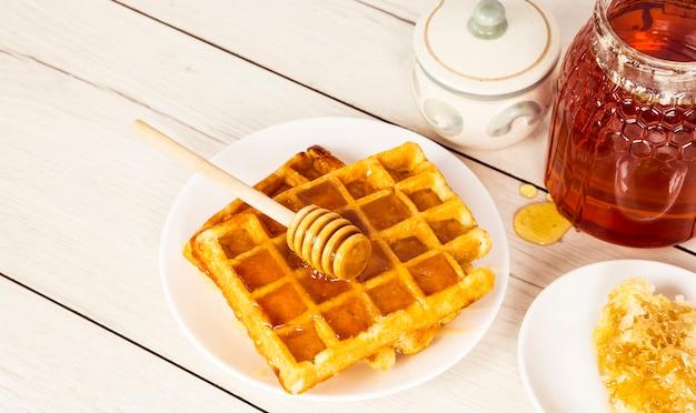 Waffles recién horneados con miel en mesa de madera