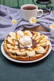 Waffles con rodajas de plátano, salsa de caramelo y crema batida con una taza de té