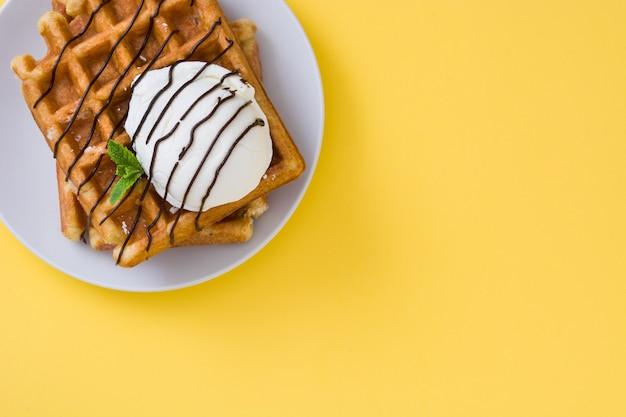 Waffles con salsa de chocolate, helado y menta en amarillo