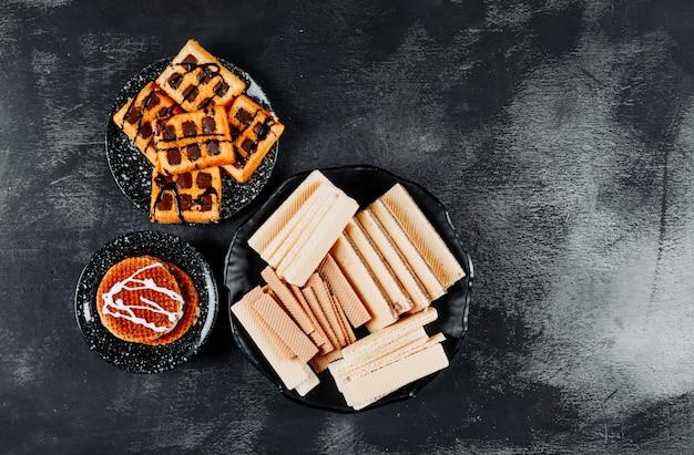 Waffles en tazones con vista superior de cookies en un espacio de fondo negro con textura para texto