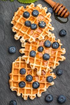 Waffles vieneses con miel y bayas frescas, arándanos y menta sobre superficie negra, postre delicioso