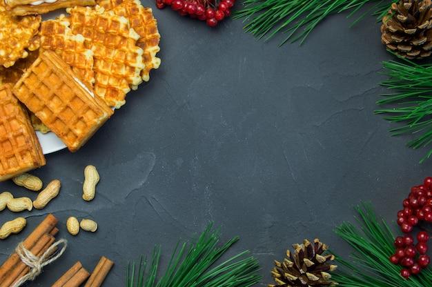 Wafle, cacahuetes y palitos de canela, rama de árbol de navidad y ashberry con cono sobre superficie de hormigón rústico oscuro