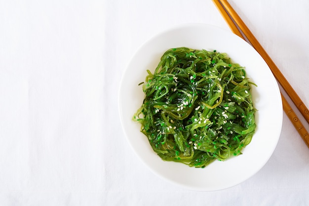 Wakame chuka o ensalada de algas con semillas de sésamo en un recipiente en la mesa blanca. comida tradicional japonesa vista superior. lay flat