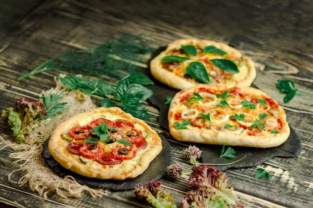 Wariety pizza en tablero de madera y varios ingredientes