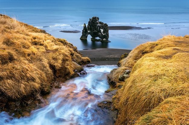 Waterfall and hvitserkur es una roca espectacular en el mar en la costa norte de islandia.