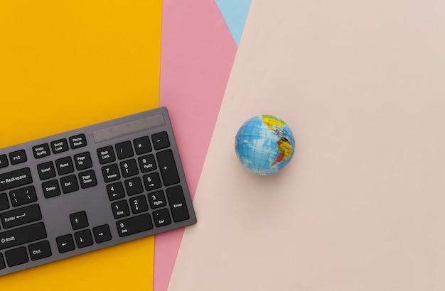 Web global. teclado de pc con globo sobre tabla coloreada
