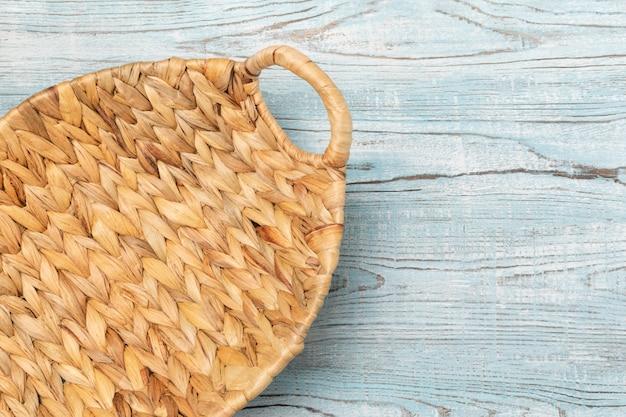 Whickered cesta vacía sobre un fondo de mesa de madera