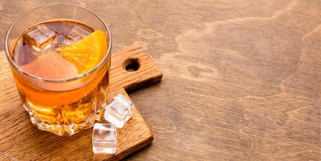 Whisky de alto ángulo y naranja con espacio de copia