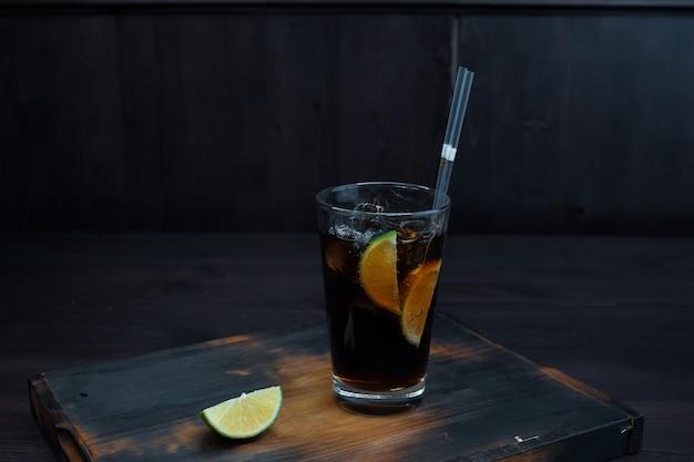 Whisky con coca cola con hielo y rodajas de limón fresco sobre una mesa de madera en el bar.