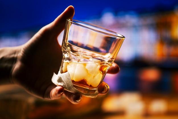Whisky cocktail con hielo en mano
