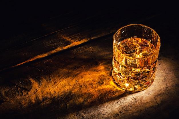 Whisky con cubitos de hielo sobre fondo de madera