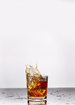 Whisky dorado en vaso con cubitos de hielo en la mesa, vista superior. espacio para texto