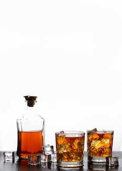 Whisky dorado en vaso con cubitos de hielo sobre fondo blanco.