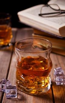 Whisky con hielo en una mesa de madera. libros antiguos cercanos.