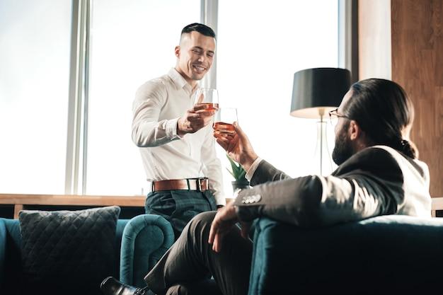 Whisky con pareja. joven apuesto hombre elegante bebiendo whisky con su socio comercial