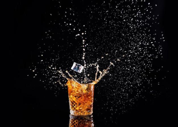 Whisky con splash sobre fondo negro, brandy en un vaso