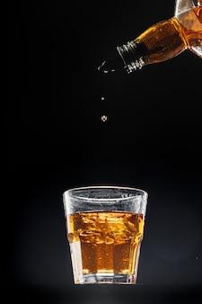 Whisky vertiendo en un vaso sobre fondo negro