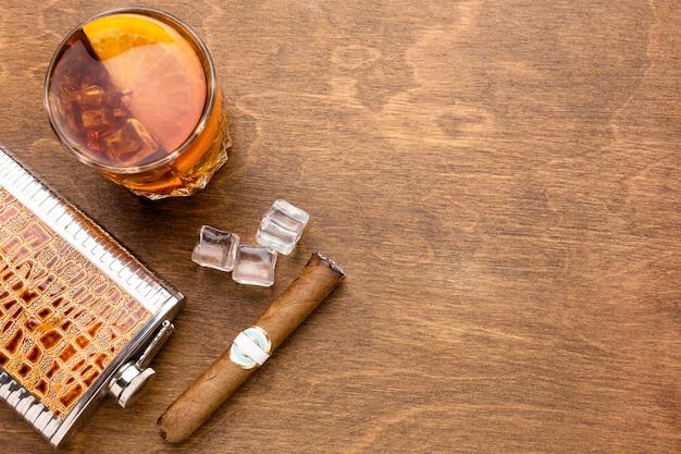 Whisky de vista superior con naranja y cigarro con espacio de copia