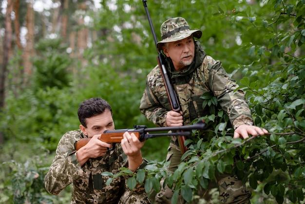 Wildfowl hunt young man está escondido y apuntando.
