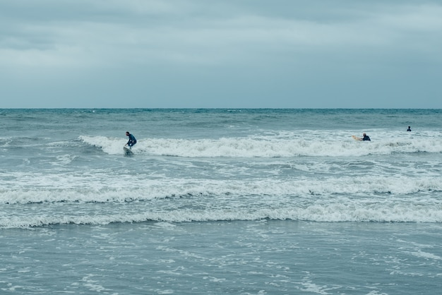 Windsurfistas tratando de montar pequeñas olas durante una tormenta.