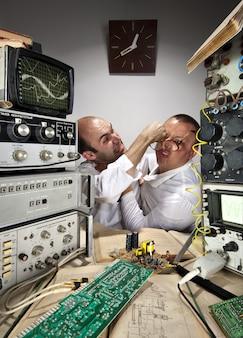 Wo científicos divertidos peleando en el laboratorio