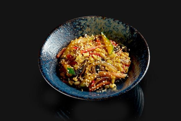 Wok de arroz de comida callejera deliciosa con verduras y cacahuetes en un plato. cocina asiática clásica. entrega de comida. aislado en negro