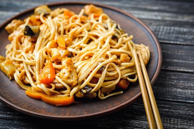 Wok chino udon fideos y palillos en mesa de madera