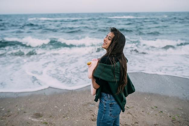 Woma joven dispara en un teléfono inteligente las olas del mar