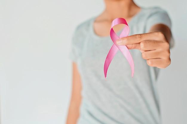 Womaen mano sosteniendo conciencia de cáncer de mama cinta rosa.