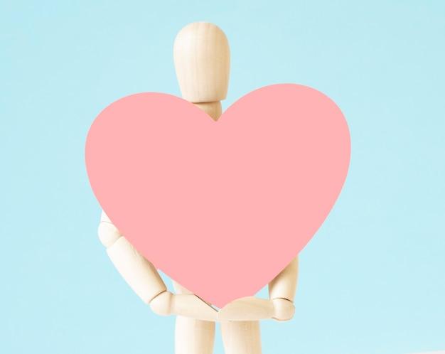 Wood man holding corazón sobre fondo de tablero de corcho espacio de copia vacío para inscripción u objetos. signo símbolo idea, concepto de amor