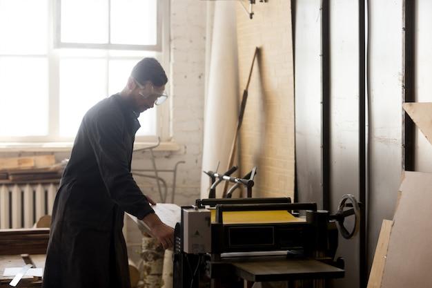 Woodworker hace madera en la máquina herramienta en la tienda