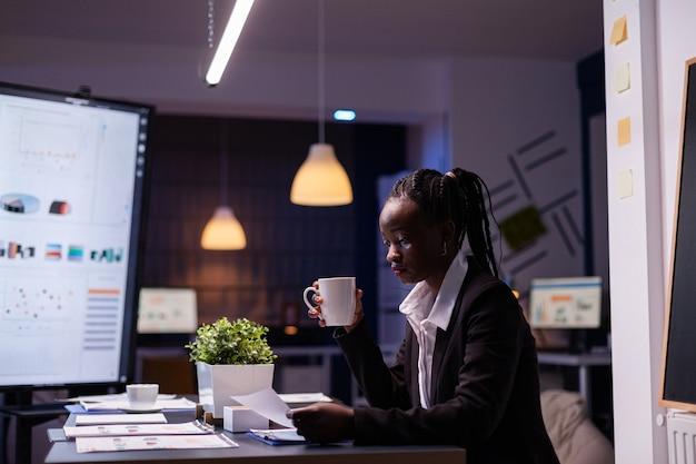 Workaholic empresaria afroamericana analizando estadísticas de marketing sobre trámites