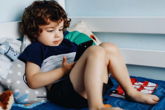 Wow, me gusta ese teléfono. bebé con teléfono inteligente. niño sentado en la cama y jugando con el teléfono móvil. llamando a mi mamá. lindo bebé tiene teléfono móvil en sus manos y mirando atentamente la pantalla.