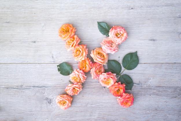 X, alfabeto de flores rosas aisladas sobre fondo de madera gris, plano lay