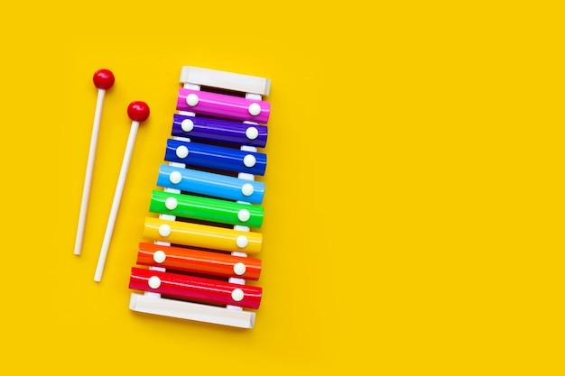 Xilófono de colores sobre fondo amarillo. copia espacio
