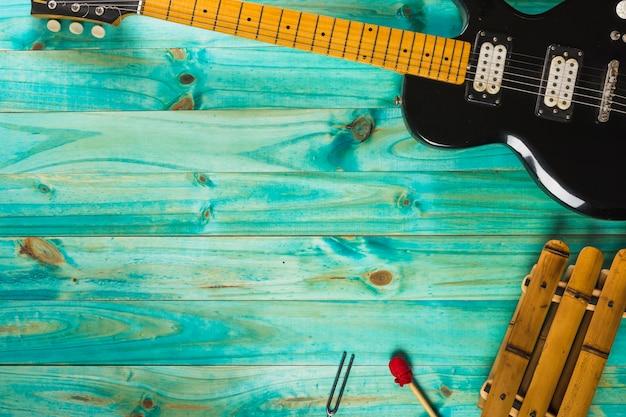Xilófono y guitarra eléctrica clásica en mesa de madera turquesa.