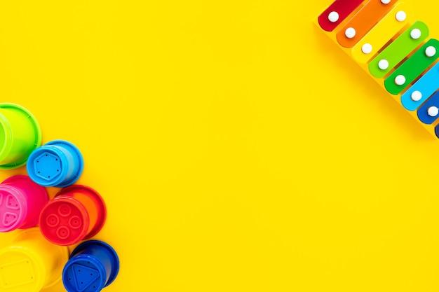 El xilófono y la pirámide de los niños del arco iris brillante en un fondo amarillo. composición con juguetes para niños, vista superior, endecha plana, espacio de copia. concepto de bebé, fondo.