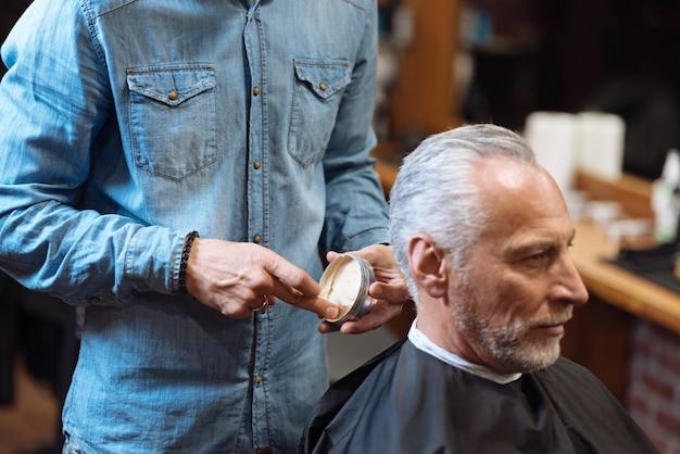 Ya se ve bien. peluquero de sexo masculino joven de pie y sosteniendo el frasco con gel para el cabello mientras su cliente senior espera a que inicie el procedimiento.