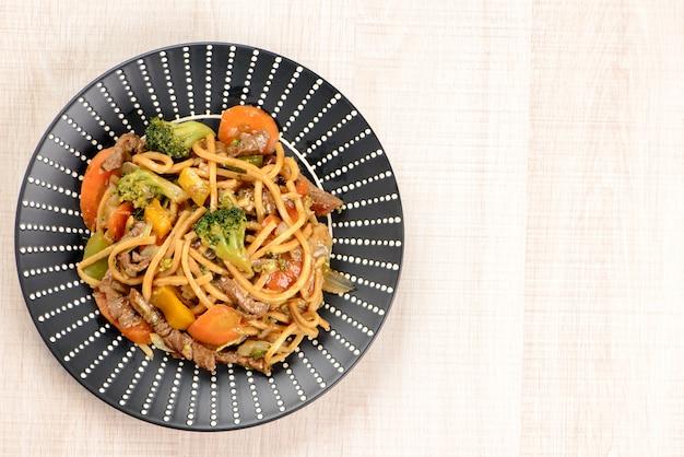 Yakisoba en un plato negro sobre una mesa