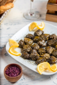 Yarpaq dolmasi, yaprak sarmasi, hojas de uva rellenas de carne y arroz, servidas con limón.