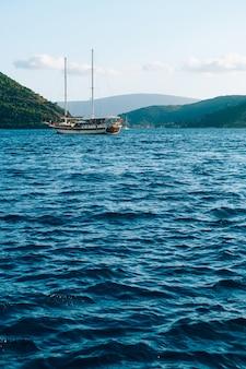 El yate se desliza sobre el agua azul con el telón de fondo de las montañas frente a la costa de la ciudad de perast