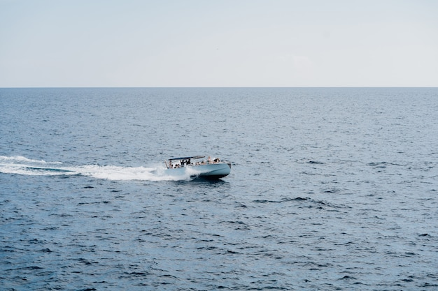 Yate a motor con turistas a bordo de velas en alta mar