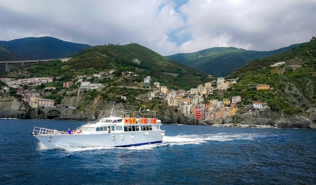 Yate navegando cerca del pueblo costero de riomaggiore, italia
