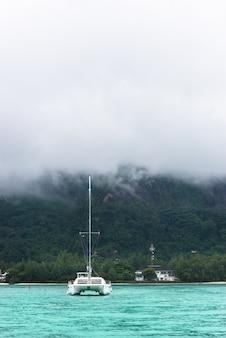 Yate en la niebla en la costa