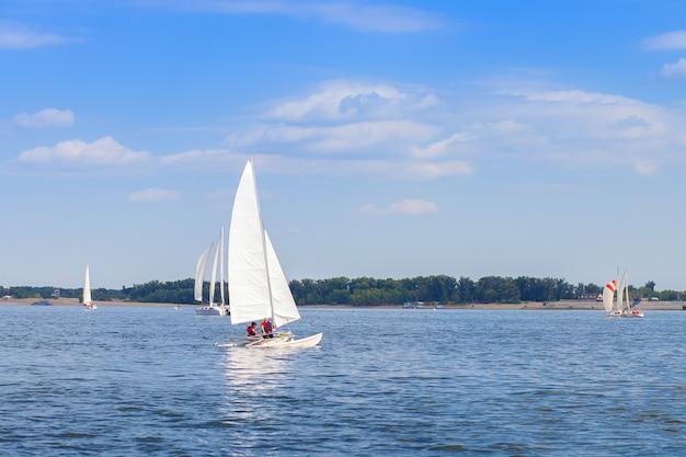 Un yate con una vela blanca flota en el río como parte de una regata de vela cerca de la ciudad de volgogrado.